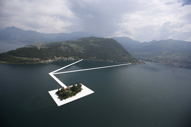 "An aerial view of the in progress installation ""The Floating Piers"" by Bulgarian-born artist Christo Vladimirov Yavachev known as Christo, on the Lake Iseo, northern Italy, Tuesday, June 7, 2016. Some 200,000 floating cubes create a 3-kilometers runway to be clad in bright yellow fabric and connecting the town of Sulzano to the small island of Monte Isola on the Iseo Lake for a 16-day outdoor installation opening on June 18 through July 3. (Photo by Luca Bruno/AP Photo)"