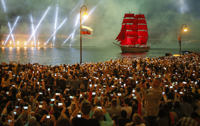 People watch fireworks and a brig with scarlet sails floating on the Neva River during the Scarlet Sails festivities marking school graduation in St.Petersburg, Russia, early Monday, June 24, 2019. This week graduation ceremonies and celebrations are held all over Russia as students of elementary and high schools and military academies finished their education. (Photo by Dmitri Lovetsky/AP Photo)