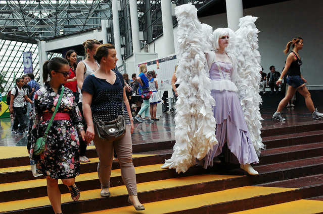 """A woman dressed like a manga character, right, attends the 15th edition of the """"Japan Expo"""" exhibition,  in Villepinte, north of Paris, Friday, July 4, 2014. The event, which runs from July 2 to 6, is devoted to Japanese culture and entertainment. (Photo by Thibault Camus/AP Photo)"""