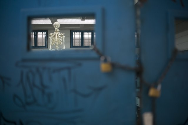 In this June 1, 2016 photo, a skeleton hangs inside a classroom used to teach evolution, locked up to keep teaching material from getting stolen, at a public high school in Caracas, Venezuela. The school locks the heavy metal gate at its sole entrance each day, making the building feel even more like a prison but students seem to be glad for the extra protection. (Photo by Ariana Cubillos/AP Photo)