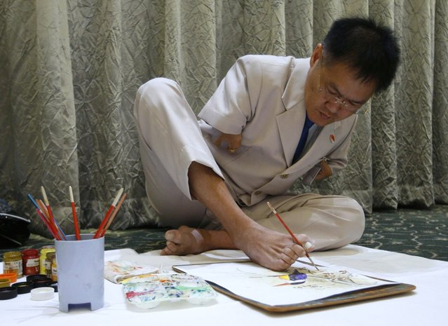 Ng Ah Kwai, 50, of Penang, Malaysia, who was born with deformed arms, paints with his foot during the Mouth and Foot Painting Convention in Singapore May 1, 2012