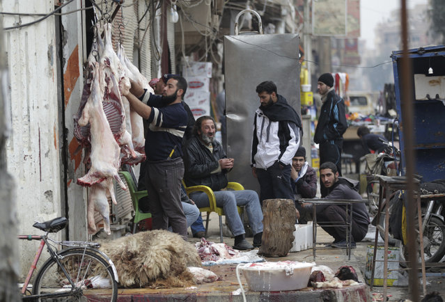 A butcher works outside a shop as people sit near him in Deir al-Zor, eastern Syria December 7, 2013. (Photo by Khalil Ashawi/Reuters)