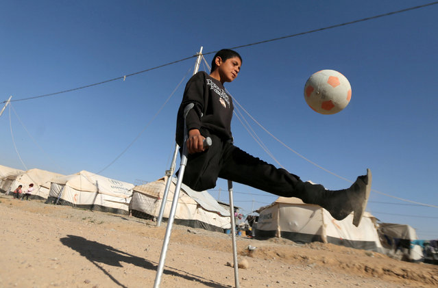 Displaced Iraqi boy Jasim Abudllah Jasim, 13, who according to his family lost his leg in an air strike in Baiji, plays football in Debaga camp, on the outskirts of Erbil, Iraq November 24, 2016. (Photo by Mohammed Salem/Reuters)