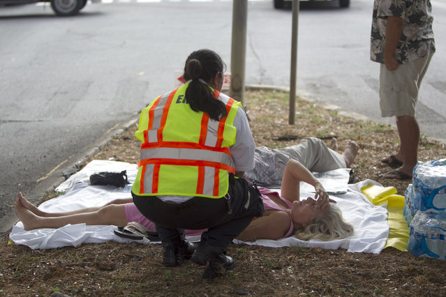 A paramedic checks on a woman, lying on a median, after she and others exited the Marco Polo apartment complex as firefighters continue to battle a blaze at the high-rise, Friday, July 14, 2017, in Honolulu. (Photo by Marco Garcia/AP Photo)
