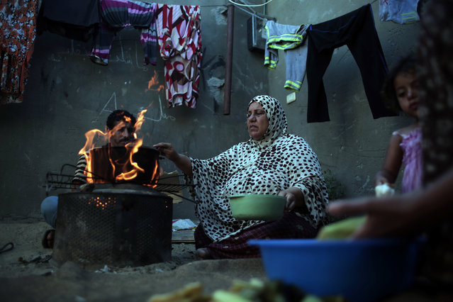 In this Monday, June 20, 2016 photo, a Palestinian woman makes a fire to prepare a Ramadan dinner, inside her house in el-Zohor slum, on the outskirts of Khan Younis refugee camp, southern Gaza Strip. (Photo by Khalil Hamra/AP Photo)