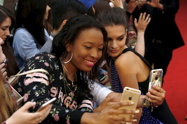 "Actor Emily Ratajkowski poses with fans for a selfie as she arrives  for the European premiere of ""We are your friends"" at Brixton Oval in London, Britain August 11, 2015. (Photo by Luke MacGregor/Reuters)"