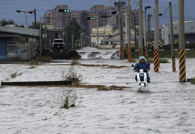A motorcyclist rides through a flooded street in Ilan county, July 23, 2014. Typhoon Matmo hit Taiwan on Wednesday, bringing heavy rain and strong winds, shutting financial markets and schools. It passed the island and headed into China, downgraded from typhoon to tropical storm. (Photo by Reuters/Stringer)