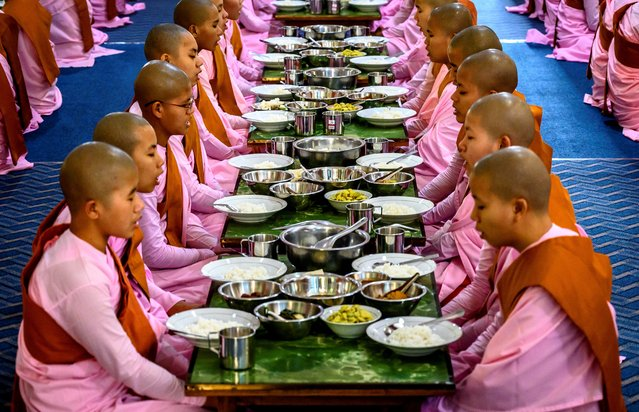 This photograph taken on January 15, 2020 shows Buddhist novice nuns praying before breakfast at a monastic school in Sagaing outside Mandalay. In keeping with Buddhist traditions, both nuns and monks refrain from eating from midday until breakfast the following morning. Myanmar is a Buddhist-majority country. (Photo by Mladen Antonov/AFP Photo)