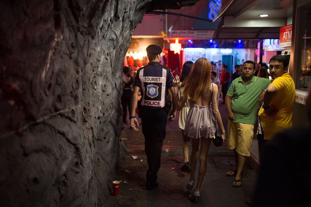 After a robbery is reported, Leo Oner, a member of FTPA, patrols Pattaya's Walking Street on July 31, 2014 in Pattaya, Thailand. Since 2002, members of the Foreign Tourist Police Assistants (FTPA) of Pattaya have been assisting local police on Walking Street, Pattaya's main nightlife area. Members of the FTPA carry handcuffs, batons, and pepper spray, and are charged primarily with assisting foreign visitors and the Thai police, as well as breaking up fights and catching thieves. (Photo by Taylor Weidman/Getty Images)