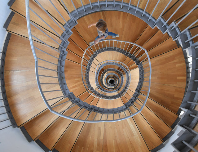 A woman walks down a spiral staircase at Gottesaue castle in Karlsruhe, Germany, 30 June 2016. The castle houses the University of Music Karlsruhe. The castle dates back to the 16th century. (Photo by Uli Deck/EPA)