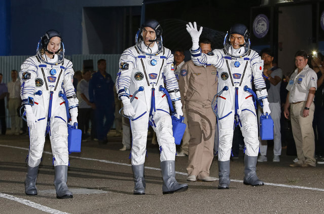 U.S. astronaut Kate Rubins, left, Russian cosmonaut Anatoly Ivanishin, centre, and Japanese astronaut Takuya Onishi, members of the main crew of the expedition to the International Space Station (ISS), walk to report to members of the State Committee prior to the launch of Soyuz MS space ship at the Russian leased Baikonur cosmodrome, Kazakhstan, Thursday, July 7, 2016. (Photo by Shamil Zhumatov/Pool Photo via AP Photo)