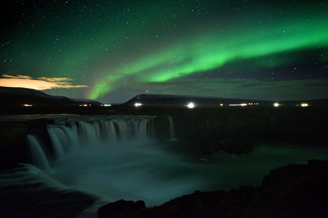 The aurora borealis, also known as Northern Lights, is seen over Godafoss waterfall, in the municipality of Thingeyjarsveit, east of Akureyri, in northern Iceland on October 14, 2018. (Photo by Mariana Suarez/AFP Photo)