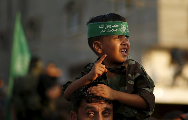 A Palestinian boy wears a Hamas headband watches  Hamas militant during a military parade marking the first anniversary of the killing of Hamas's military commanders Mohammed Abu Shammala and Raed al-Attar, in Rafah in the southern Gaza Strip August 21, 2015. (Photo by Suhaib Salem/Reuters)