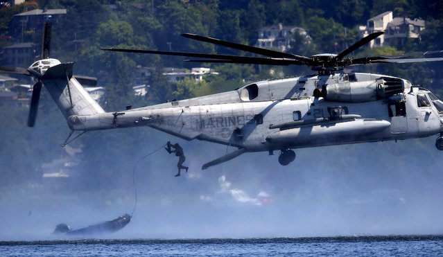 A U.S. Marine jumps from a helicopter after a raft is dropped as part of a demonstration during the Seafair Air Show, Sunday, August 3, 2014, in Seattle. (Photo by Ted S. Warren/AP Photo)