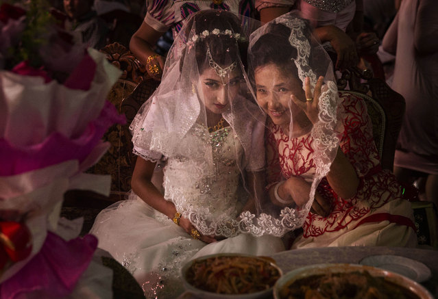 A Uyghur bride talks with a friend at her  wedding celebration on August 2, 2014 in Kashgar, Xinjiang Province, China. (Photo by Kevin Frayer/Getty Images)