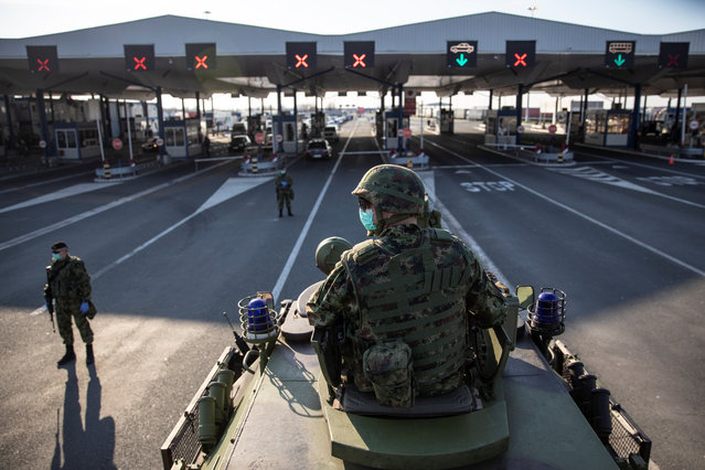 A Serbian army soldier sits on top of armoured personal carrier at the Serbia's Batrovci border crossing with Croatia's Bajakovo, as the number of coronavirus (COVID-19) cases grow around the world near Batrovci, Serbia, March 18, 2020. Under the new set of restrictions, the Serbian military will take over all border crossings and maintain guard at over a dozen state-operated camps for illegal migrants from Asia and the Middle East. (Photo by Marko Djurica/Reuters)