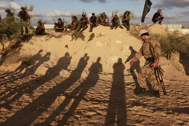 The shadows of observers on the ground as Palestinian militants from Al Nasser Brigades, an armed wing of the Popular Resistance Committees (PRC), participate in a training session in Khan Younis, southern Gaza Strip, Friday, September 27, 2013. (Photo by Hatem Moussa/AP Photo)