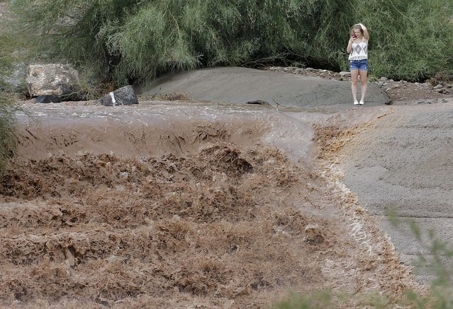 A girl photographs the flash flood waters from the Sonoran Desert overrun Skunk Creek, Tuesday, August 19, 2014, in northwestern Phoenix. Flooding from heavy rain in the Phoenix area has forced authorities to close several major roads, including a portion of Interstate 17 about 25 miles north of the city. (Photo by Matt York/AP Photo)