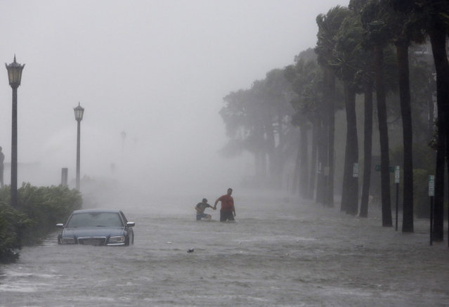 Pedestrians walk by a flooded car on a street as Tropical Storm Irma hits Charleston, S.C., Monday, September 11, 2017. (Photo by Mic Smith/AP Photo)