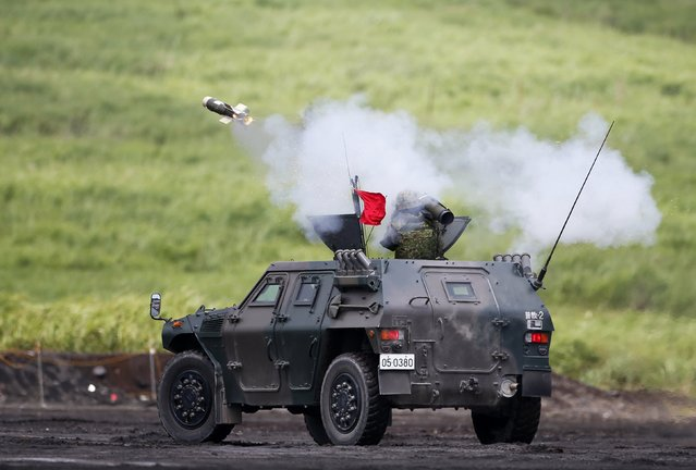 A Japanese Ground Self-Defense Force soldier on an armoured vehicle fires a guided anti-tank missile during an annual training session near Mount Fuji at Higashifuji training field in Gotemba, west of Tokyo, August 19, 2014. (Photo by Yuya Shino/Reuters)
