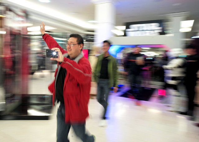 """A shopper films a video of himself as he arrives at a Sydney department store after midnight September 4, 2015, to purchase new merchandise from the """"Star Wars: The Force Awakens"""" on """"Force Friday"""". (Photo by Jason Reed/Reuters)"""