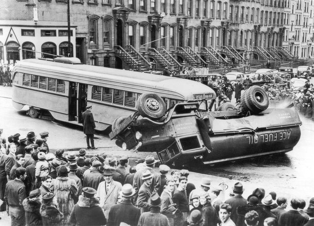 Crowds of people look at the aftermath of an accident in which a lorry has been hit by a bus and then overturned, circa 1950. (Photo by Hulton Archive)
