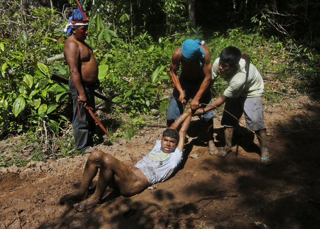 Ka'apor Indian warriors tie up and remove the pants of a logger during a jungle expedition to search for and expel loggers from the Alto Turiacu Indian territory, near the Centro do Guilherme municipality in the northeast of Maranhao state in the Amazon basin, August 7, 2014. (Photo by Lunae Parracho/Reuters)