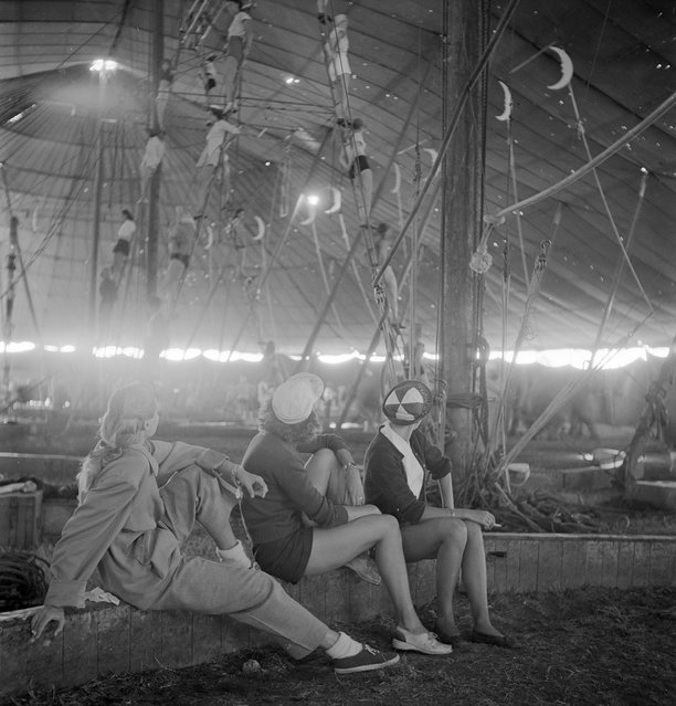 Three circus girls sitting on a wooden plank and watching a group of aerialists rehearsing with ropes for the Ringling Bros. and Barnum & Bailey Circus in Sarasota, FL in 1949. (Photo By Nina Leen/Time Life Pictures/Getty Images)