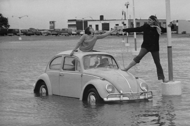 Sally Gomez drives to rescue of friend Michele Moore in flooded parking lot at Hyannis, Mass., September 9, 1969, after torrential rains of Hurricane Gerda flooded low areas of Cape Cod. Ann Davis of Osterville stands up in roof opening to lend a hand. Sally and Michele are from Centerville on the Cape. (Photo by Frank C. Curtin/AP Photo)