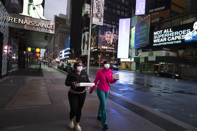 People carry takeout food in New York's Times Square, Wednesday night, April 29, 2020, during the coronavirus pandemic. President Donald Trump said Wednesday the federal government will not be extending its coronavirus social distancing guidelines once they expire Thursday. (Photo by Mark Lennihan/AP Photo)