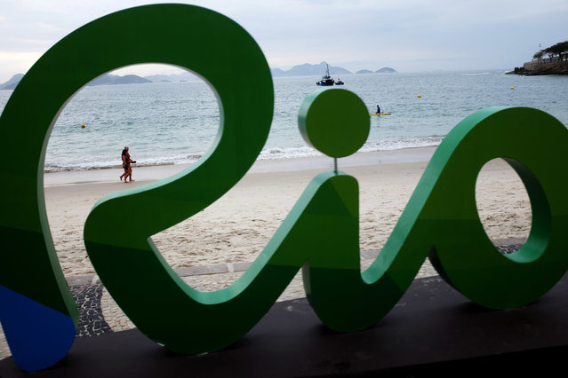 A couple walks along Copacabana beach ahead of the upcoming 2016 Summer Olympics in Rio de Janeiro, Brazil, Thursday, August 4, 2016. The iconic Copacabana beach will be the starting point for the road cycling race, marathon swimming and triathlon competitions during the Olympics. (Photo by David Goldman/AP Photo)