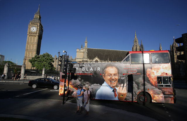 A london bus with an advertisment for a film about former British Prime Minister Tony Blair passes near the Houses of Parliament in central London on July 18, 2016. Prime Minister Theresa May warned Monday that the threat from nuclear weapons was increasing as she pressed MPs to approve the replacement of the ageing submarines that carry Britain's nuclear arsenal. MPs will vote Monday evening on whether to approve the construction of four new submarines to carry the Trident missile system and their nuclear warheads, at a cost of £41 billion (49 billion euros, $54 billion). (Photo by Daniel Leal-Olivas/AFP Photo)