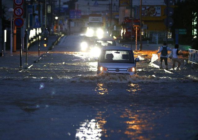 Vehicles drive through a flooded street in Joso, Ibaraki prefecture, north of Tokyo, Thursday, September 10, 2015. (Photo by Shizuo Kambayashi/AP Photo)