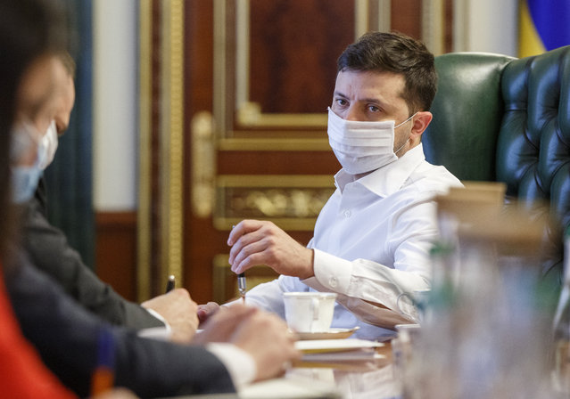 Ukrainian President Volodymyr Zelenskiy in a face mask to protect against coronavirus, discusses the COVID-19 situation in the country with officials in his office in Kyiv, Ukraine, Wednesday April 22, 2020. (Photo by Ukrainian Presidential Press Office via AP Photo)