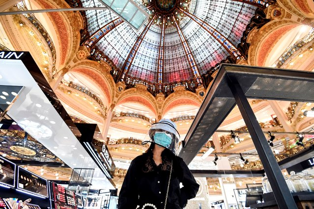 A woman wearing protective face shield shops at the Galeries Lafayette on the first day of the reopening of the luxury general store, on May 30, 2020, in Paris, as France eases lockdown measures taken to curb the spread of the Covid-19 pandemic (novel coronavirus). (Photo by Alain Jocard/AFP Photo)