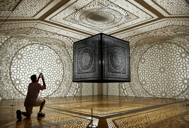 "A man photographs Anila Quayyum Agha's ""Intersections"" art work on the first day of ArtPrize at the Grand Rapids Art Museum in Grand Rapids, Mich. on Wednesday, September 24, 2014. (Photo by Emily Rose Bennett/AP Photo/The Grand Rapids Press)"