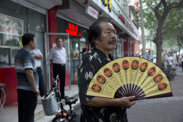 A resident holds a fan with photos of Chinese generals near plain clothes security personnel in the background near the Tianjin No. 2 Intermediate People's Court in northern China's Tianjin Municipality on Tuesday, August 2, 2016. (Photo by Ng Han Guan/AP Photo)