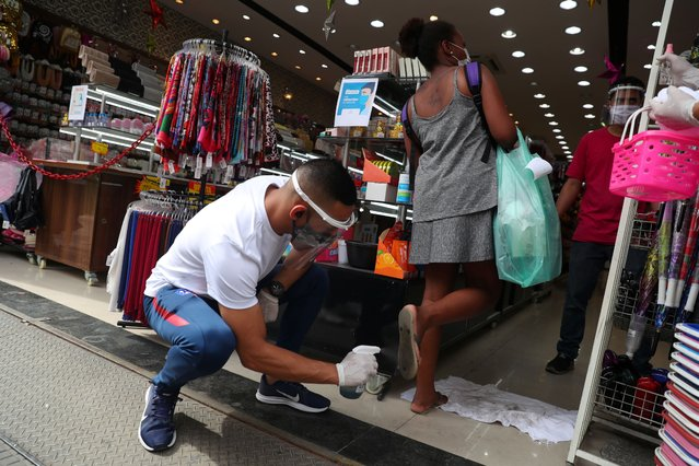 A man sprays alcohol in a woman's shoes before she enters a shop as the city hall eases restrictions on the first day of open commerce since the beginning of quarantine, due to the coronavirus disease (COVID-19) outbreak, in Sao Paulo, Brazil, June 10, 2020. (Photo by Amanda Perobelli/Reuters)