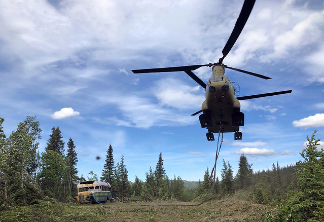 """In this photo released by the Alaska National Guard, Alaska Army National Guard soldiers use a CH-47 Chinook helicopter to removed an abandoned bus, popularized by the book and movie """"Into the Wild"""", out of its location in the Alaska backcountry Thursday, June 18, 2020, as part of a training mission. Alaska Natural Resources Commissioner Corri Feige, in a release, said the bus will be kept in a secure location while her department weighs various options for what to do with it. (Photo by Sgt. Seth LaCount/Alaska National Guard via AP Photo)"""