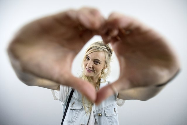 A model poses for a portrait while making a heart symbol with her hands backstage before the Michael Kors Spring/Summer 2016 collection presentation during New York Fashion Week in New York, September 16, 2015. (Photo by Carlo Allegri/Reuters)