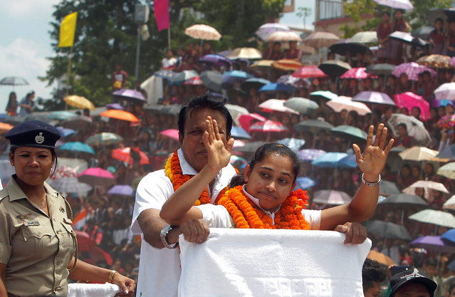 Gymnast Dipa Karmakar waves as she stands in a vehicle during her felicitation parade after her return from Rio Olympics, upon her arrival on the outskirts of Agartala, India, August 22, 2016. (Photo by Jayanta Dey/Reuters)
