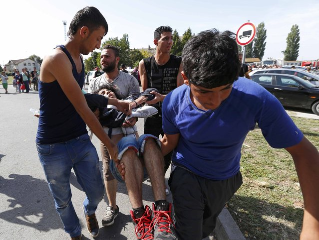 A wounded man is attended after clashes between Syrian and Afghan migrants at the train station in Beli Manastir, Croatia September 18, 2015. (Photo by Laszlo Balogh/Reuters)