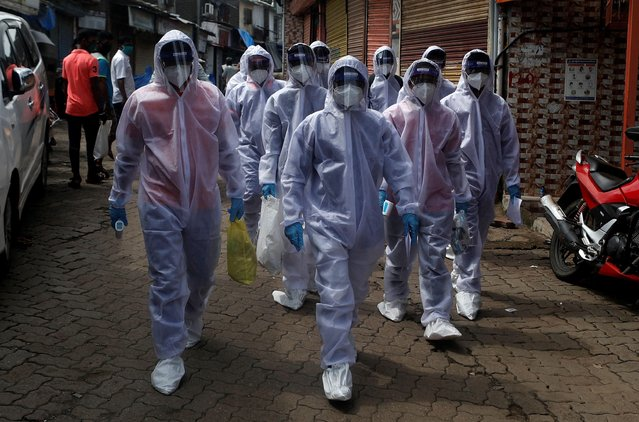 Healthcare workers wearing personal protective equipment (PPE) walk towards different localities before the start of a check-up camp for the coronavirus disease (COVID-19) in Mumbai, India on June 27, 2020. (Photo by Francis Mascarenhas/Reuters)