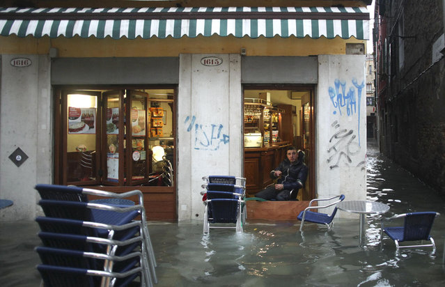 A man rests in a shop in a flooded street during a period of seasonal high water in Venice November 11, 2012. The water level in the canal city rose to 149 cm (59 inches) above normal, according to local monitoring institute Center Weather Warnings and Tides. (Photo by Manuel Silvestri/Reuters)