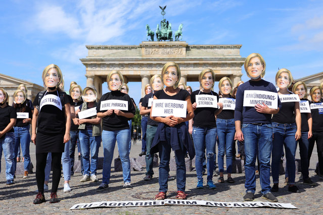 Protesters wear masks with the image of German Minister for Food, Agriculture and Consumer Protection Julia Kloeckner during a demonstration for future-proof EU agricultural reform at Pariser Platz near the Brandenburg Gate in Berlin, Germany, 30 June 2020. The protesters demand of Minister Kloeckner to pull the strings during the final negotiations on the EU Common Agricultural Policy reform (CAP) to ensure the redistribution of funds towards farms, animals rights and Climate issues. Germany takes over the EU Council Presidency on July 1st. (Photo by Omer Messinger/EPA/EFE)