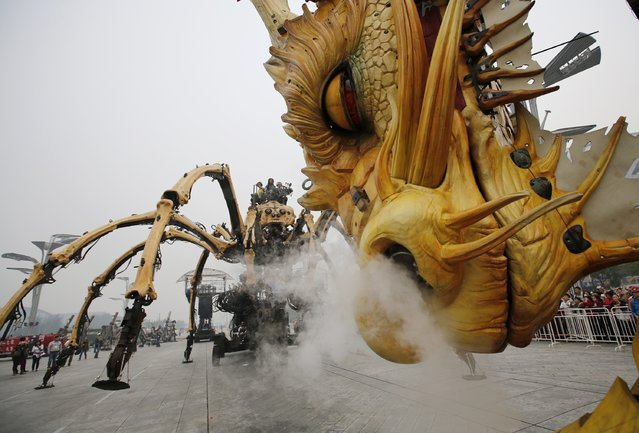"""Mechanical installations named """"Long Ma"""" (R) and """"The Spider"""" are operated at a rehearsal of the Long Ma performance in front of the National Stadium, also known as the Bird's Nest, in Beijing October 10, 2014. (Photo by Kim Kyung-Hoon/Reuters)"""