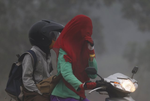A girl cover her face while riding a motorcycle as haze shrouds a street near Tanjung Siapi Api port in Palembang, on the Indonesian island of Sumatra, September 19, 2015. Indonesia will take 30 days to bring smouldering forest fires under control, the national disaster management agency said on Friday, as smog from the fires pushes pollution in Southeast Asia to record highs. (Photo by Reuters/Beawiharta)