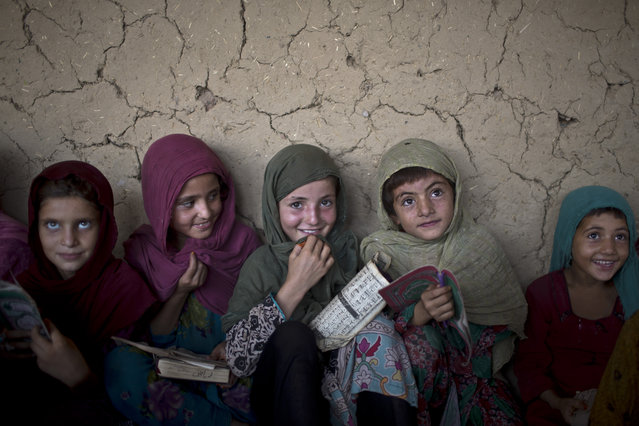 In this Monday, August 11, 2014, photo, Afghan refugee girls listen to their teacher during their daily Madrassa, or Islamic school, at a mosque on the outskirts of Islamabad, Pakistan. (Photo by Muhammed Muheisen/AP Photo)