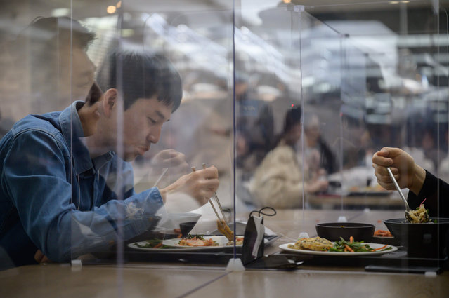 """In this file photo taken on April 9, 2020 employees sit behind protective screens as part of preventative measures against the COVID-19 novel coronavirus, as they eat in a cafeteria at the offices of Hyundai Card credit card company in Seoul. - Hyundai Card has implemented reduced working hours and staggered lunch breaks, while South Korea – once grappling with the largest coronavirus outbreak outside China – has seen a continued decline in new virus cases thanks to """"aggressive tests and active participation in social distancing"""", authorities said. (Photo by Ed Jones/AFP Photo)"""