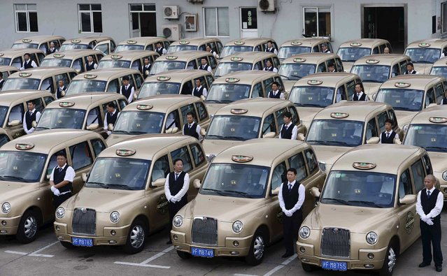 "Drivers stand next to brand new Geely Englon TX4 taxis, which were created based on the ""London cab"", during an inauguration ceremony in Shanghai, October 11, 2014. Qiangsheng, Shanghai's largest taxi company, unveiled its first batch of 50 Geely Englon TX4 taxis to the public on Saturday. The China-made ""London cabs"" are painted in champagne gold colour, instead of the well-known black, local media reported. (Photo by Reuters/Stringer)"